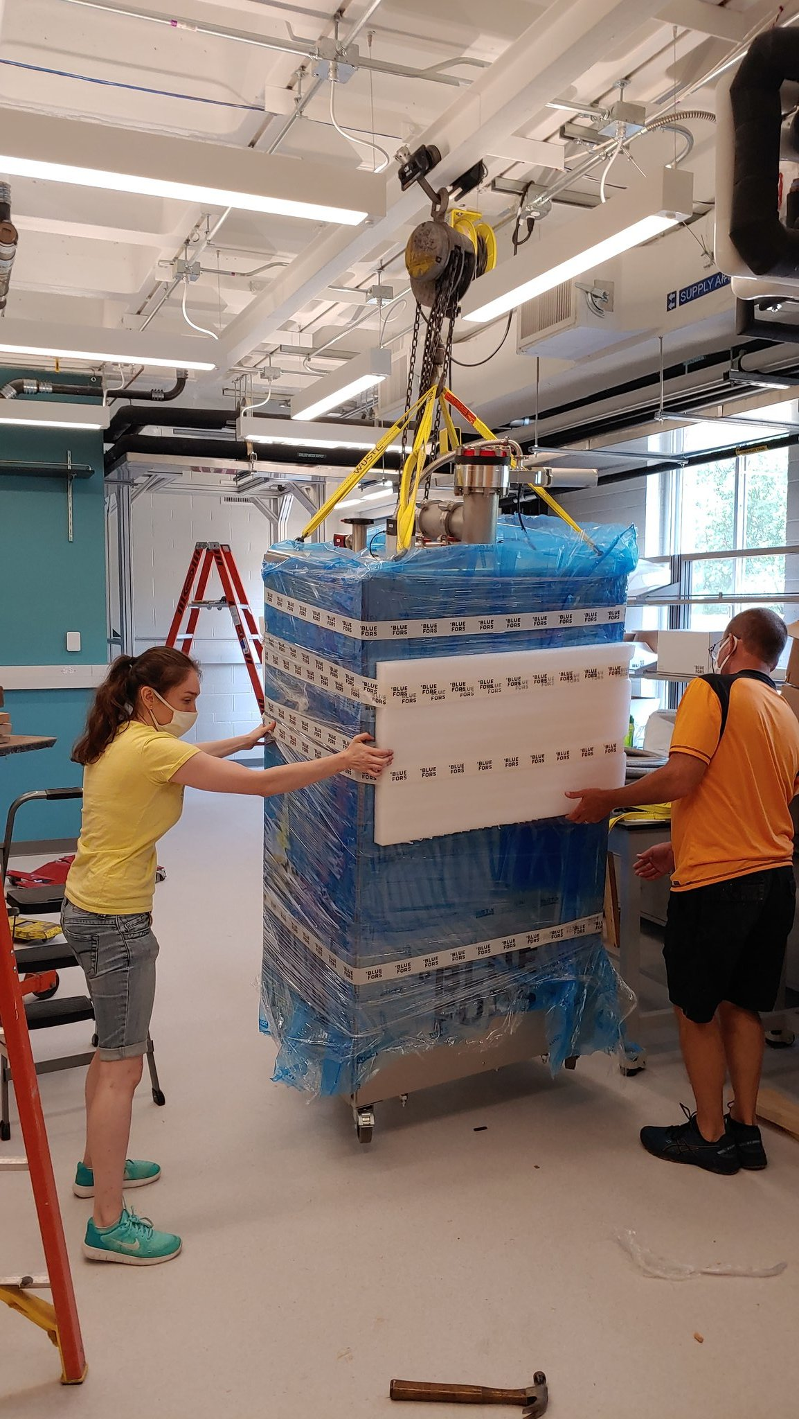 Nagy and Simburger moving in new lab equipment.